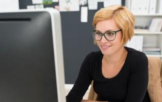 Kvinde sidder ved computer og laver sin egen hjemmeside
